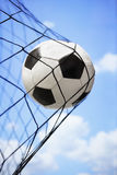 Soccer ball in back of the goal net Stock Photos