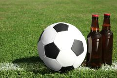 Soccer ball with beverage on green football field gras. S stock photography