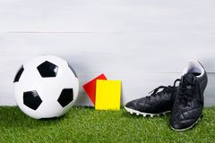 Soccer ball, black boots and two penalty cards for the judge, stand on the grass, on a gray background royalty free stock images
