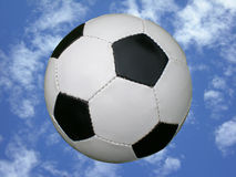 Soccer ball in blue sky. A traditional black and white soccer ball in front of blue sky background Royalty Free Stock Photos