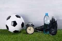 Soccer ball, a bottle of water, black boots and an alarm clock stand on the grass, on a gray background stock image