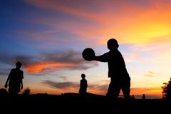 Soccer ball boy playing sunset. Silhouette of three young boys playing soccer in field Stock Photography