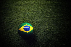 Soccer ball with Brazil flag. On grass field, 3d render royalty free stock photography