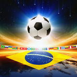 Soccer ball with brazil flag. Abstract sports background - soccer ball, Brazil flag, bright light, stars in night sky stock photo