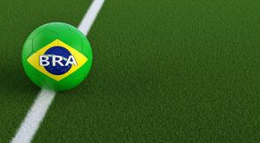 Soccer ball in brazils national colors on a soccer field. Copy space on the right side - 3D Rendering. Soccer ball in brazils national colors on a soccer field Royalty Free Stock Images