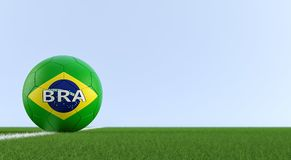 Soccer ball in brazils national colors on a soccer field. Copy space on the right side - 3D Rendering. Soccer ball in brazils national colors on a soccer field Royalty Free Stock Image