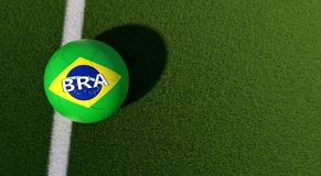 Soccer ball in brazils national colors on a soccer field. Copy space on the right side. 3D Rendering Stock Photo