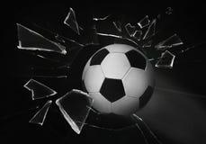 Soccer ball breaking up glass against black background