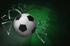 Soccer ball breaking up glass against green background