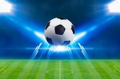 Soccer ball, bright spotlights, illuminates green soccer stadium Stock Photos