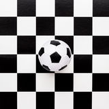 Soccer ball on chequered pattern Royalty Free Stock Photo