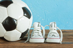 Soccer ball and children's shoes Stock Photo