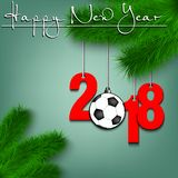 Soccer ball and 2018 on a Christmas tree branch. Happy New Year and numbers 2018 and soccer ball as a Christmas decorations hanging on a Christmas tree branch Stock Image