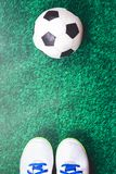 Soccer ball and cleats against green artificial turf. Soccer ball, cleats against green artificial turf, top view with copy space, football concept stock images