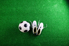 Soccer ball and cleats against green artificial turf, studio sho Royalty Free Stock Image