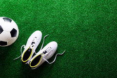 Soccer ball and cleats against green artificial turf, studio sho Royalty Free Stock Photography