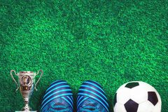 Soccer ball, a cup and cleats against green artificial turf. Soccer ball, cleats and a silver cup against green artificial turf, top view with copy space stock photos