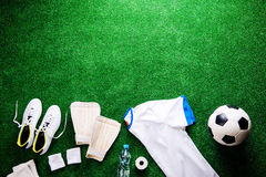 Soccer ball,cleats and various football stuff against artificial Royalty Free Stock Image
