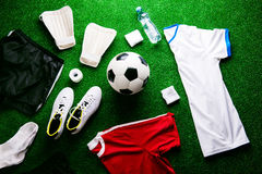 Soccer ball,cleats and various football stuff against artificial Royalty Free Stock Images