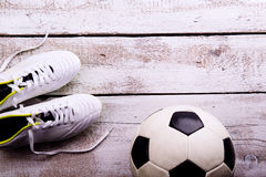 Soccer ball, cleats on white wooden floor, studio shot Royalty Free Stock Photography