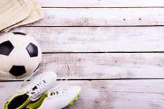 Soccer ball, cleats on white wooden floor, studio shot Stock Photography