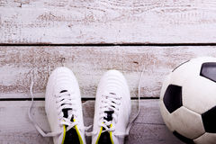 Soccer ball, cleats on white wooden floor, studio shot Royalty Free Stock Photos