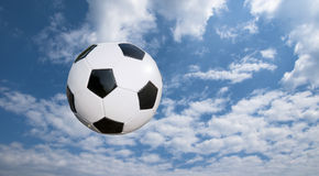 Soccer ball and cloudscape. Black and white soccer ball in mid-air with cloudscape in background Stock Photography