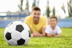 Soccer ball and dad with son. In the stadium stock images