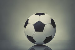 Soccer ball on dark background. Soccer ball with reflection on a table on a gray background Stock Photos