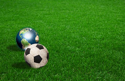 Soccer ball and earth on green grass Royalty Free Stock Photo