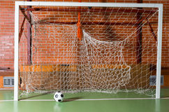 Soccer ball in an empty goal post. On an all weather indoor court in a brick building, close up view Royalty Free Stock Images
