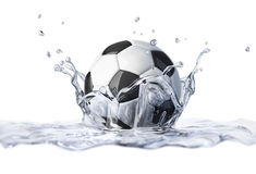 Soccer ball falling into clear water, forming a crown splash. Royalty Free Stock Photos