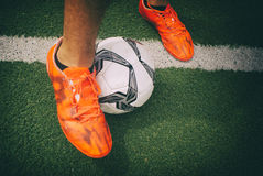 Soccer ball and feet on grass Royalty Free Stock Image