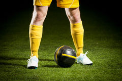 Soccer ball and a feet of a soccer player Royalty Free Stock Images