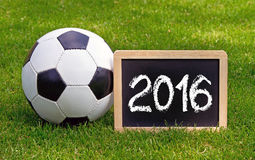 2016 soccer ball and field. Chalkboard with 2016 in white chalk next to soccer ball on grassy pitch Royalty Free Stock Photo