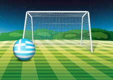 A soccer ball at the field with the flag of Greece Royalty Free Stock Images