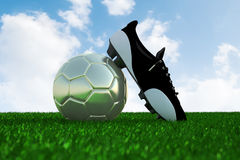 Soccer ball on field and soccer shoe Royalty Free Stock Photography