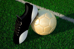 Soccer ball on field and soccer shoe Stock Photo