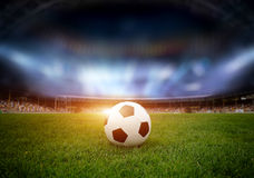 Soccer ball on the field of stadium. With light Stock Image
