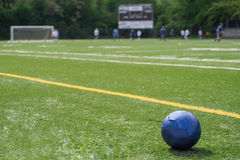 Soccer ball on field with teams, goal, scoreboard in background. A blue, soccer ball is in the lower, right corner of the image. A softly blurred background Royalty Free Stock Photos