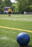 Soccer ball on field with teams, scoreboard, referee in background Stock Image