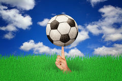 Soccer ball on finger with sky. And clouds on background Stock Image