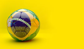 Soccer ball with flag. 3d Soccer ball with Brazil 2014 flag isolated on yellow Royalty Free Stock Images