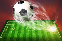 Soccer ball flying from football field Stock Photos