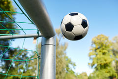 Soccer ball flying into football goal net on field. Sport, soccer and game - ball flying into football goal net stock photo