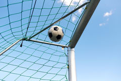 Soccer ball flying into football goal net over sky. Sport, soccer and game - ball flying into football goal net over blue sky royalty free stock image