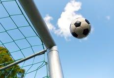 Soccer ball flying into football goal net over sky Royalty Free Stock Photos