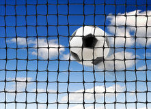 Soccer ball flying into the gate Stock Images