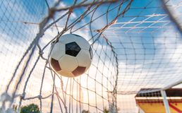Soccer ball flying in the net. Scored goal, win, success , sunset in the background, closeup shot ball flying royalty free stock image