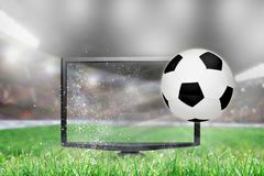 Soccer Football Flying Out of TV Screen in Stadium. Soccer ball flying out of shattering TV screen in stadium with copy space. Concept of realistic 3D or 4D TV stock photography